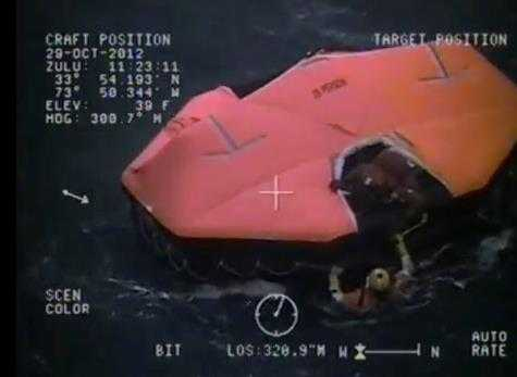 A Coast Guard rescue swimmer approaches on of two lifeboats where the crew of HMS Bounty sought shelter after abandoning ship. Screenshot from U.S. Coast Guard video.